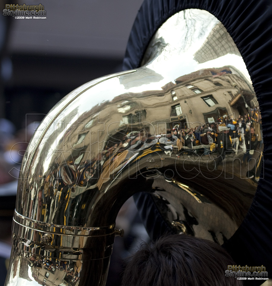 Crowd reflects in the tuba