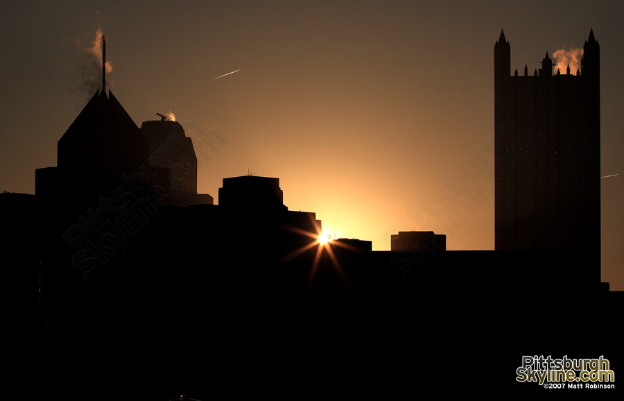 The sun peeks over Gateway Center at sunrise
