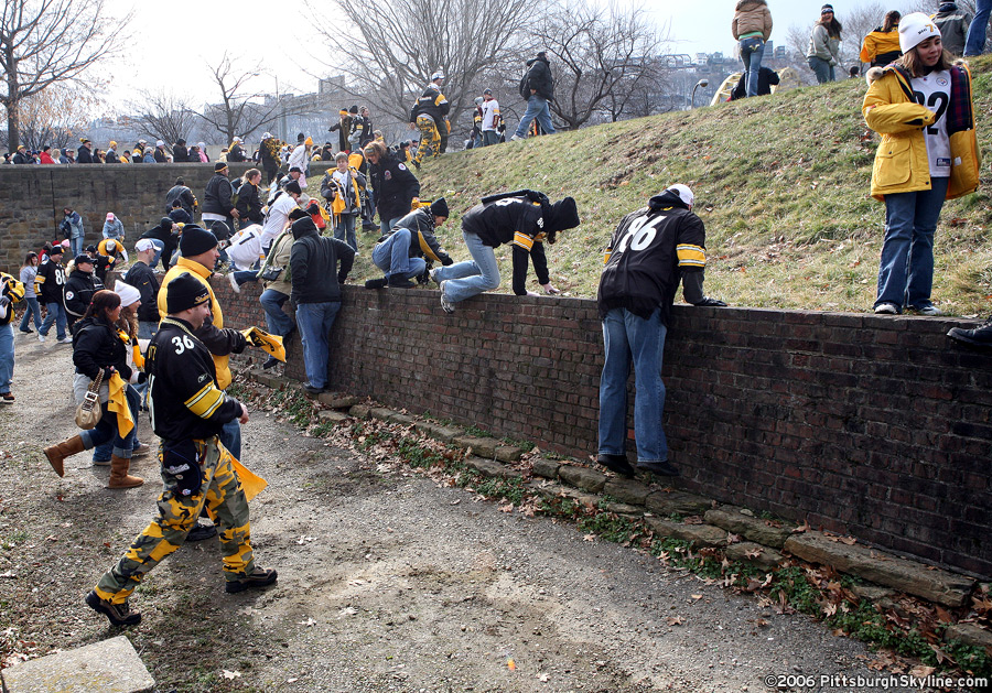 Fans scale a wall at Fort Duquesne at the Point.